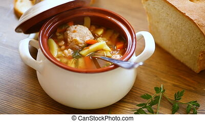 vegetable soup with beans and meatballs in a ceramic bowl