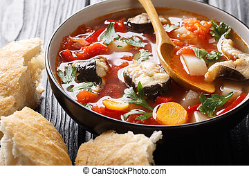 Vegetable soup with eel fish and tomatoes closeup in a bowl. horizontal