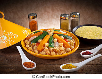 Vegetable tagine with cous cous and spices on wooden table.