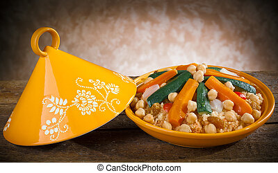 Vegetable Tajine with cous cous on wooden table.