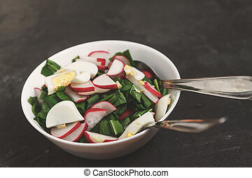 Vegetable vegan salad of ramson, radish, green onions and boiled eggs in a white plate on a dark concrete background, in retro treatment. Close-up, top view, flatlay. The concept of healthy nutrition.