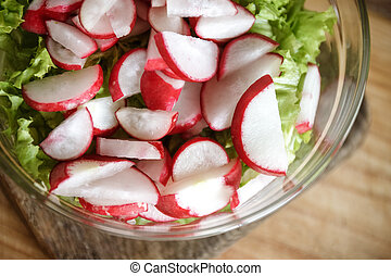 Vegetable vegan salad of wild garlic, radish, spring onions, cabbage and lettuce in a large transparent dish on an antique wooden background. Close-up, top view, flatlay. White background. The concept of healthy proper nutrition.