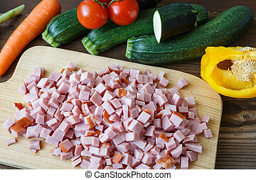 Vegetable with sliced meat on cutting board.