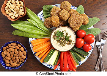 Colorful vegetables, lettuce, falafels and humus on a plate on a wooden background.