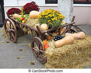 Vegetables and pumpkins on hay in a wooden cart, the season of harvest on farm thanksgiving