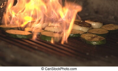 vegetables are roasted on fire and coal on barbecue grill in...