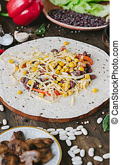 Vegetables, beans and cheese over tortilla bread - vegetarian mexican salad tacos.