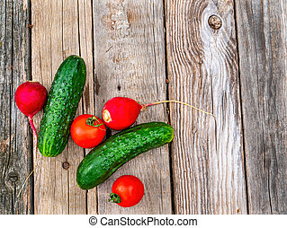 Vegetables cucumbers with tomatoes on a wooden table.