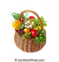 Fresh kitchen garden vegetables in a wicker basket on a white.