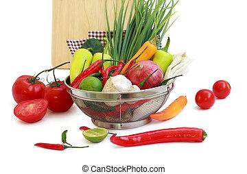 vegetables in metal colander on white background