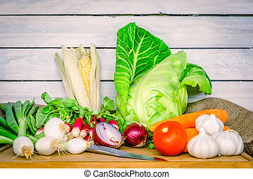 Vegetables on a wooden table with a knife