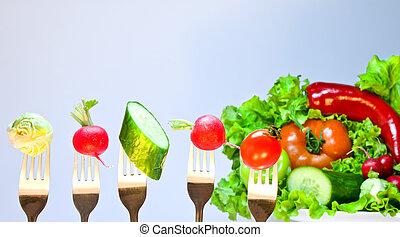 Vegetables on forks on a background of fresh vegetables