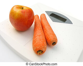 Vegetables on scale - Carrots and red apple on a white ...