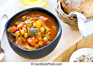 Vegetables soup with chickpea by bread loaf