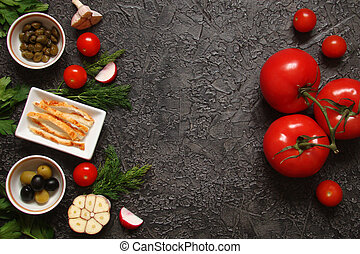 Vegetables, tomatoes, herbs, olives, capers, garlic on textured black background
