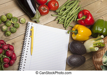 Vegetables with book and pen on wooden surface - High angle...