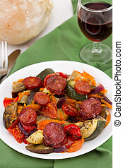 vegetables with chorizo on the plate with glass of red wine