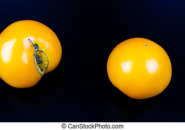 Vegetables yellow tomatoes on a black background.