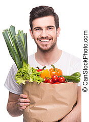 Vegetables - Young man is holding a bag full of vegetables,...