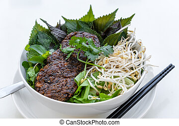 Vegetarian Bun Cha, popular vietnamese food. Bun Cha and fried pancakes with tofu cheese and mushrooms in white bowl on the table