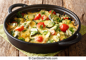 Vegetarian casserole with zucchini cheese and cherry tomatoes close-up in a pan. horizontal