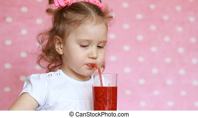 Vegetarian drink. A happy child drinks a raspberry smoothie through a straw and laughs. Close-up portrait of a cute girl who enjoys a refreshing tasty raspberry juice. Pink background