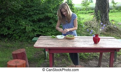 vegetarian farmer girl hands husk fresh green peas on red wooden table. 4K