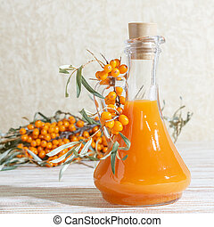Vegetarian food, healthy nutrition, preserving the harvest of homemade ripe juicy sea-buckthorn, preparing fresh healthy vitamin drink and healing broth. Bottle of juice and branches of orange sea buckthorn