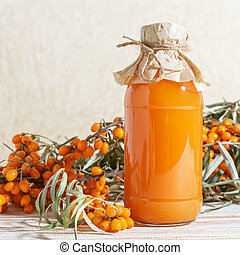 Vegetarian food, healthy nutrition, preserving the harvest of ripe juicy sea-buckthorn, preparing fresh healthy vitamin drink and healing broth. Jug with juice and branches of orange sea buckthorn