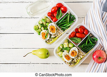 Vegetarian meal prep containers with eggs, brussel sprouts, green beans and tomato. Dinner in lunch box. Top view. Flat lay