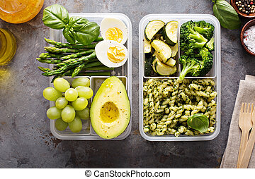 Vegetarian meal prep containers with eggs and pasta with green pesto sauce and vegetables