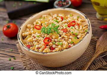 Vegetarian porridge from Turkish couscous with vegetables....