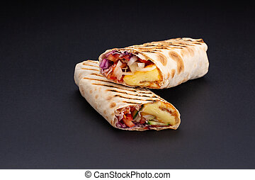 Shawarma in pita bread is cut and lies on a black reflective background. The Middle Eastern dish is prepared on the grill