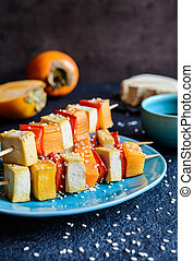 Vegetarian skewers with persimmons, tofu, pepper, sesame and soya sauce