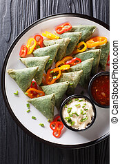 Vegetarian Spinach samosa with sauces close-up on a plate. Vertical top view