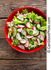 Vegetarian vegetable salad of radish, cucumbers, lettuce salad and flax seeds. Healthy vegan food. Top view