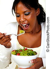 Vegetarian woman eating a attractive green salad