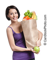 Vegetarian young woman with the packet full of different healthy food, isolated, white background