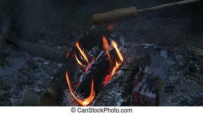 Veggie hot dog roasting on fire