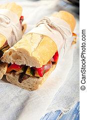 Tasty grilled vegetarian submarine sandwich with portobello mushroom, peppers, onions, zucchini and tomato