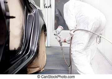 Vehicle engineer working and spraying black paint on a car...