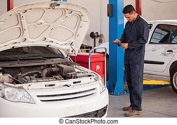 Vehicle inspection at an auto shop - Hispanic Mechanic using...