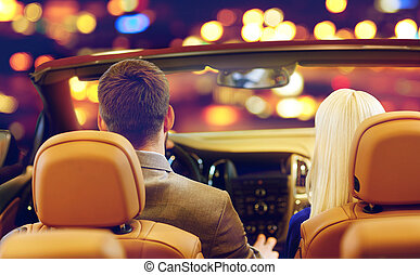 close up of couple driving in convertible car