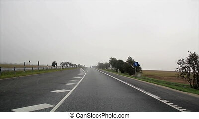 Vehicle moving on a highway where trees are found at the side