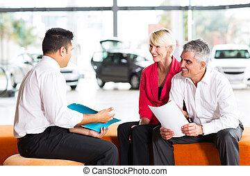 vehicle salesman explaining contract to senior couple before...