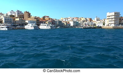 Vehicle shot from boat with pan of Agios Nikolaos, Crete