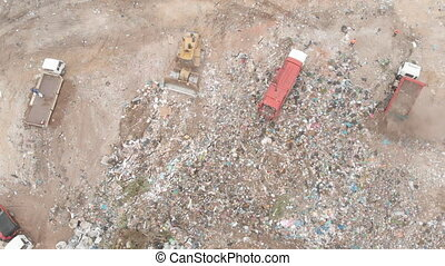 Vehicles clearing rubbish piled on a landfill full of trash