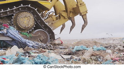 Side view close up of vehicle working and clearing rubbish piled on a landfill full of trash with vehicles working and clearing rubbish in the background in slow motion