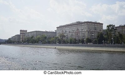 Vehicles moving as shot from the Moskva river motor boat -...