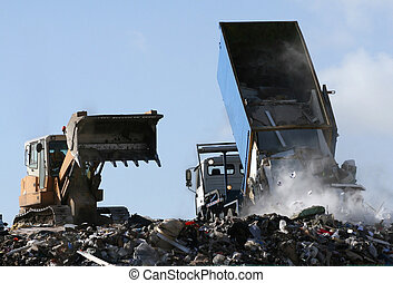 Rubbish being dumped from a truck next to a bulldozer on a landfill site